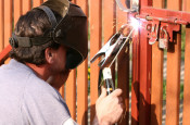 man welded hinges on the new fence