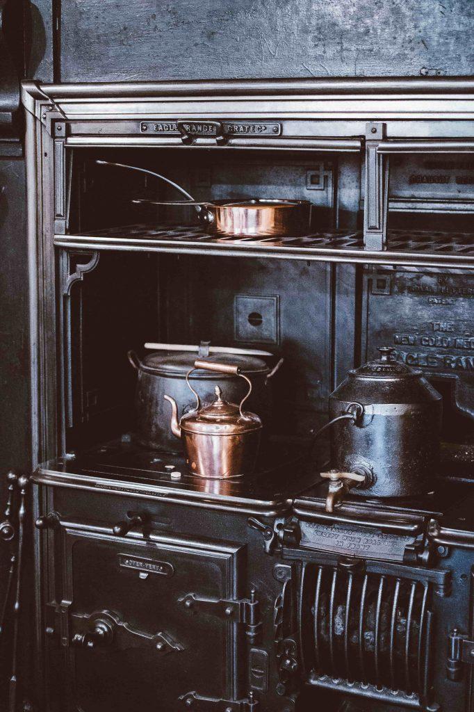 Une cuisinière à bois noire avec casseroles en cuivre