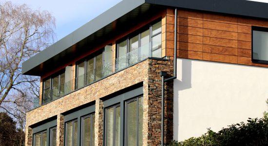 Maison neuve et moderne construite avec de la pierre, du bois et de l'aluminium