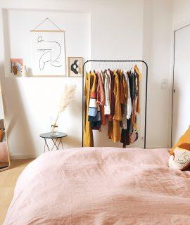 chambre avec penderie sur roulettes et miroir en pied dans un coin